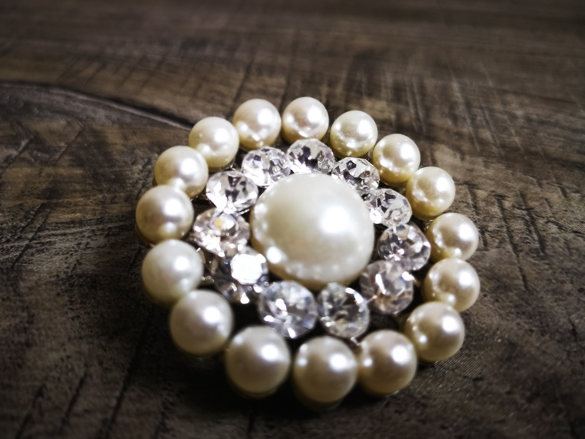 Brooch with white pearl for clothes isolated on wooden background. Brooch with diamond stone.